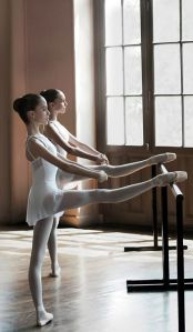 Young dancers with legs on the barre
